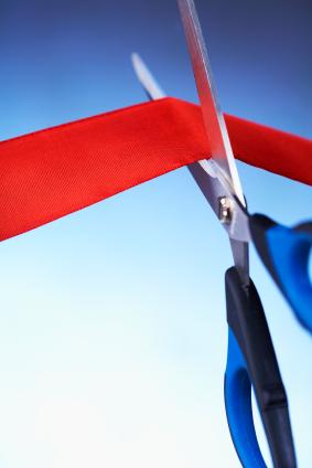 Closeup image of scissors cutting a red ribbon