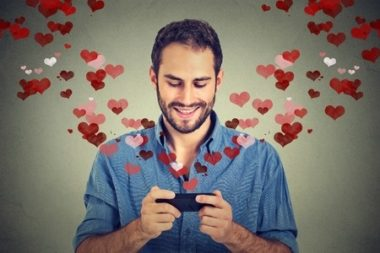 47505627 - portrait happy man sending love sms text message on mobile phone with red hearts flying away from screen isolated on grey wall background. human emotions
