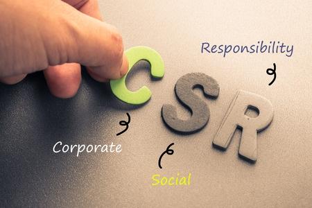 closeup hand arrange wood letters as csr abbreviation(corporate social responsibility)