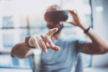 closeup of male hand.bearded young man wearing virtual reality goggles in modern coworking studio. smartphone using with vr headset in office. horizontal, blurred