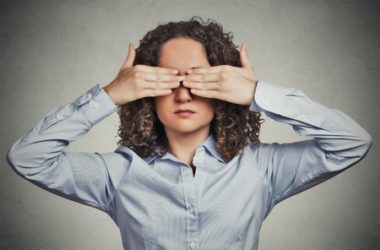 closeup portrait headshot young woman closing covering eyes with hands can't look hiding avoiding situation isolated grey wall background. see no evil concept. human emotion face expression perception