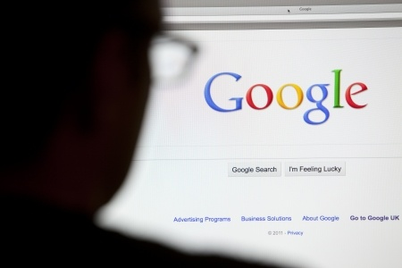 close-up of the google.com search homepage displayed on a lcd computer screen with silhouette of a man's head out of focus in the foreground.