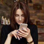 portrait of charming young brunette european lady browsing newsfeed via social networks, liking posts and typing comments, using free high-speed internet connection at coffee shop