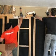 two guys removing damaged drywall