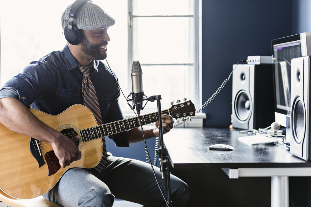 A man recording his music in his home studio.