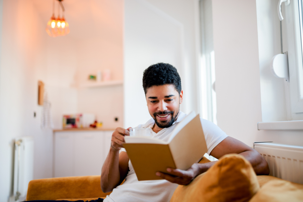 man reading a book while sitting on the sofa